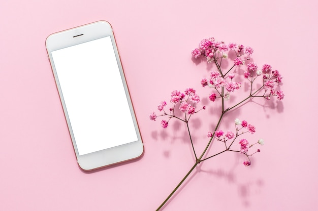 Mobile phone and pink flowers on pink pastel table