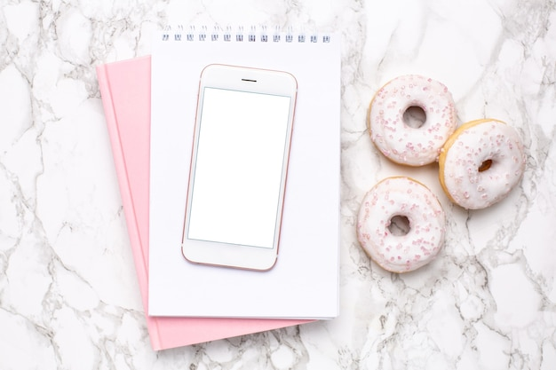 Mobile phone,pink notebook and sweet donut on a marble background
