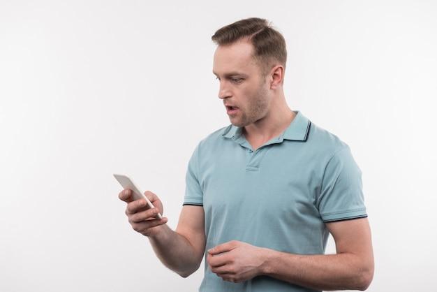 携帯電話。その画面を見ながら彼のガジェットを保持している楽しい素敵な男