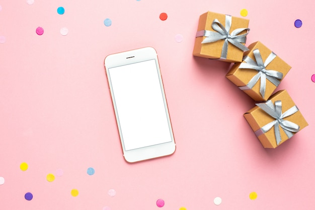 Mobile phone, present boxes and color confetti on pink table.