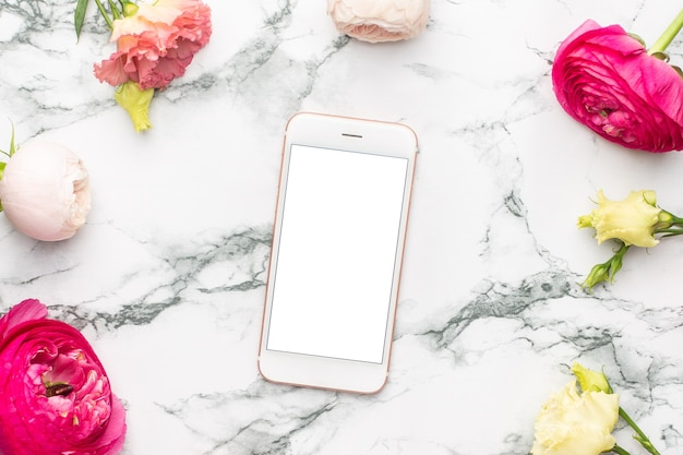 Mobile phone, ranunculi pink flower and white flower bouquet on marble background