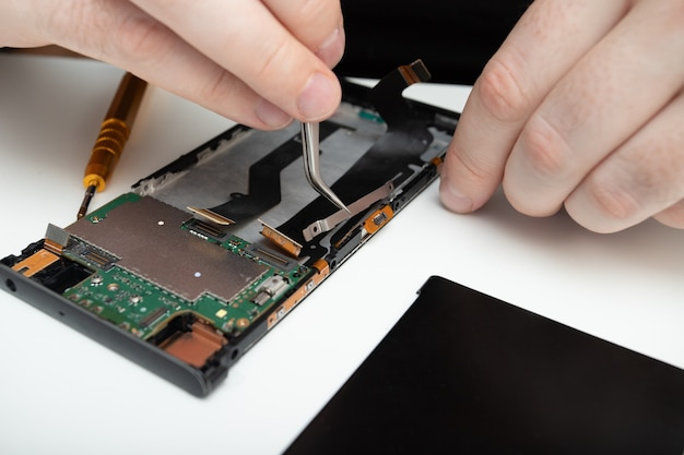 Mobile phone repair. the wizard collects a smartphone from the details