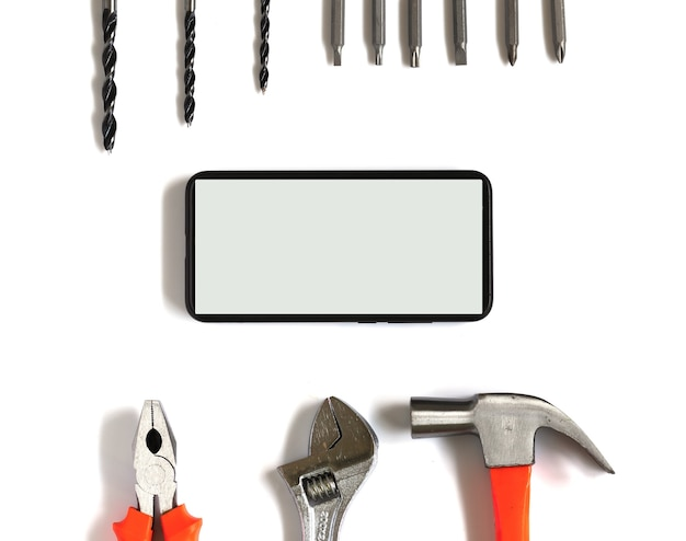 Mobile phone and set of tools space for text on white background.