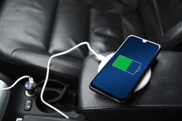 Заряжается мобильный телефон, смартфон, сотовый телефон, заряжайте аккумулятор с помощью зарядного устройства usb в салоне автомобиля. современный черный салон автомобиля