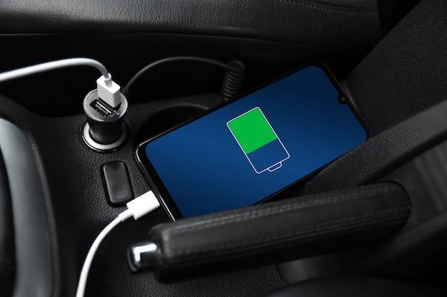 Заряжается мобильный телефон, смартфон, сотовый телефон, заряжайте аккумулятор с помощью зарядного устройства usb в салоне автомобиля. современный черный салон автомобиля.