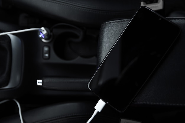 Mobile phone, smartphone charge battery, charging in the car plug close up