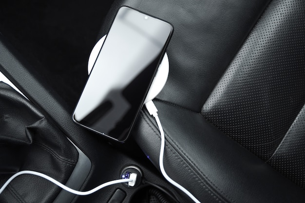 Mobile phone, smartphone charge battery, wireless charging in the car plug close up