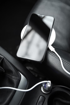 Мобильный телефон, зарядка аккумулятора смартфона, беспроводная зарядка в автомобильной вилке крупным планом