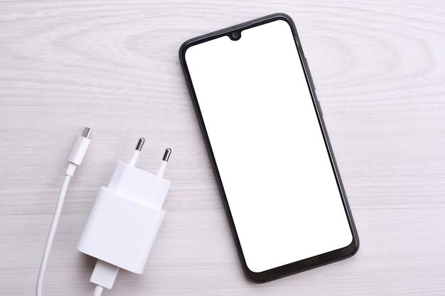 あなたのテキストのための白い画面、充電中の明るい欠陥のあるテーブル上の画像を備えた携帯電話のスマートフォン