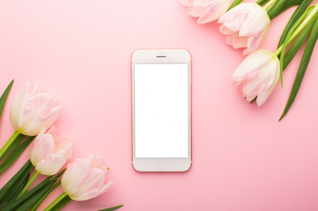 Mobile phone and spring flower pink tulips.  flat lay