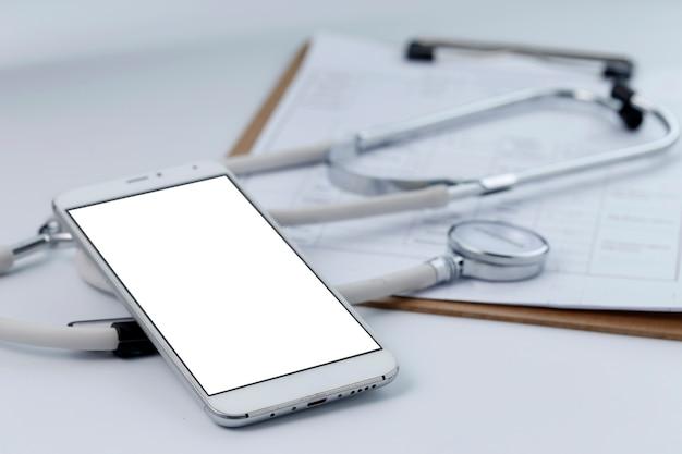 바탕 화면의 휴대 전화, 청진기 및 차트 파일 (모바일 의료, 핸드 헬드 의사 개념)