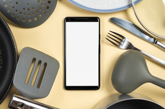 Mobile phone surrounded with utensil on beige background