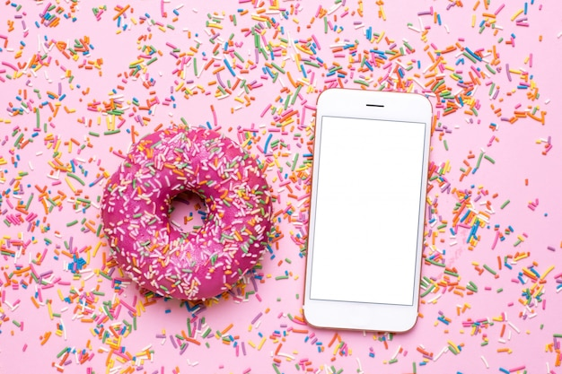 Mobile phone , sweet multicolored sprinkles and on pink pastel table in flat lay style.