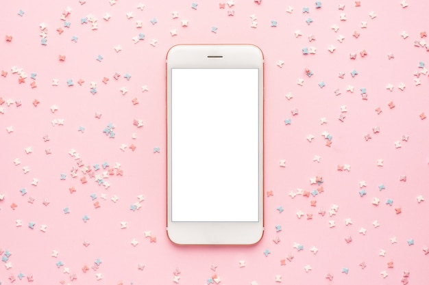 Mobile phone and sweet pastry topping on pink