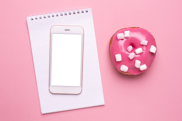 Mobile phone and sweet pink donut with marshmallows on a pink background flat lay