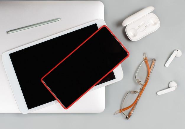 白い背景の上のラップトップの近くに携帯電話、タブレット、イヤホン、メガネ