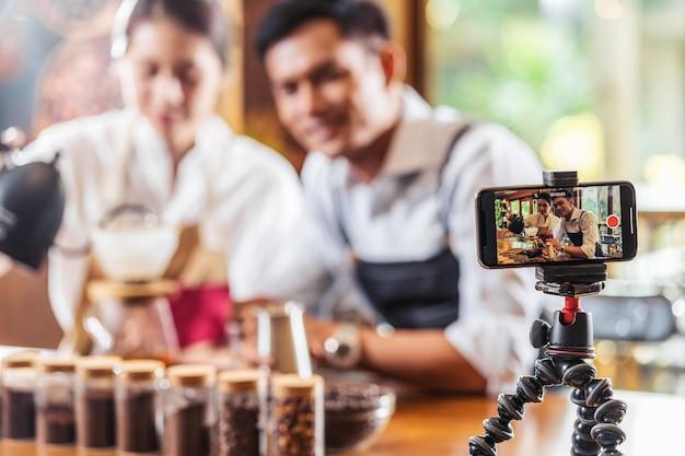 コーヒーを滴下するコーヒーショーを提示する2つのアジアのバリスタにビデオを撮る携帯電話