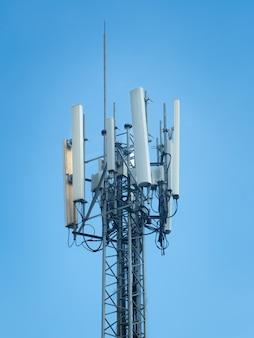 Телекоммуникационная башня мобильного телефона против голубого неба
