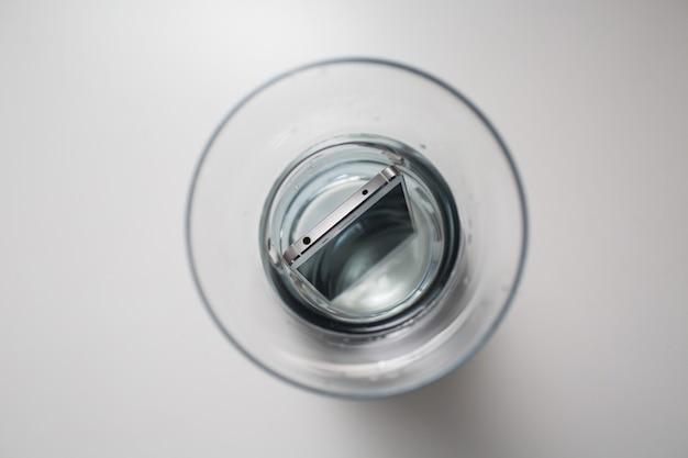 Мобильный телефон водонепроницаем в емкости с водой. Premium Фотографии