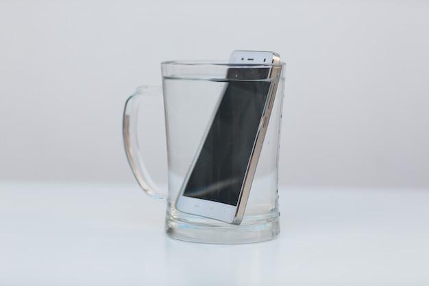 Мобильный телефон водонепроницаем в емкости с водой.