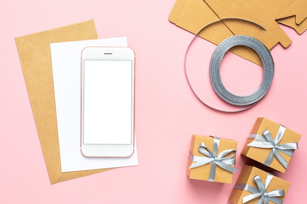 Mobile phone and white card with gift in box composition for birthday