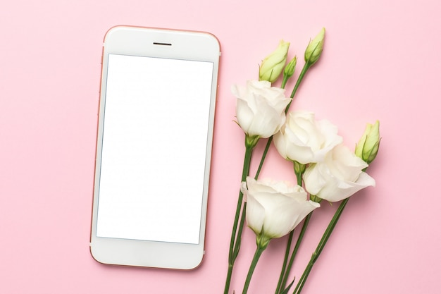 Mobile phone, white flower and notebook on pink