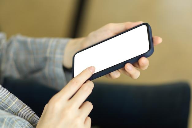 Макет белого экрана мобильного телефона на женских руках с размытым фоном