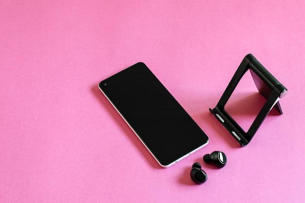 ピンクの上に携帯電話、ワイヤレスイヤホン、電話スタンド