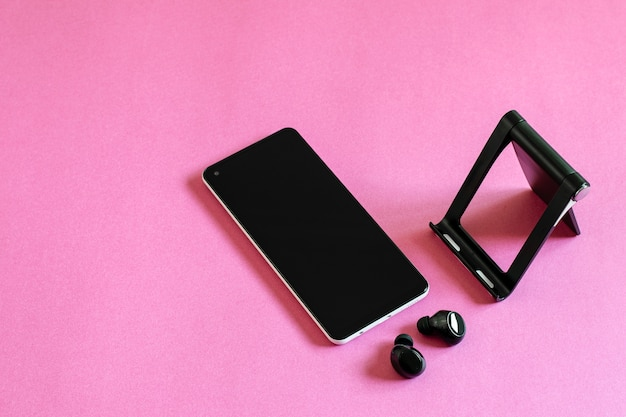 Mobile phone, wireless earphones and phone stand on the pink