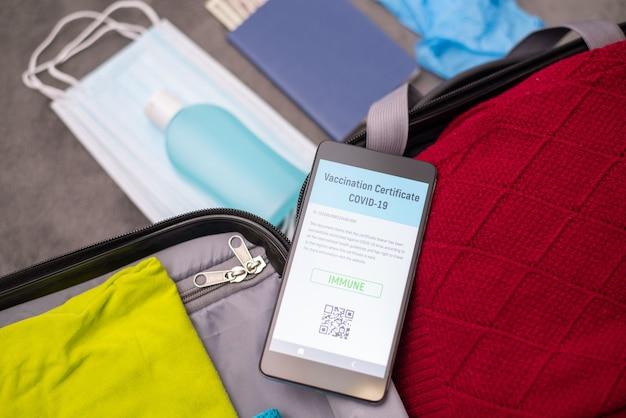 Мобильный телефон с цифровым сертификатом о вакцинации на чемодане перед поездкой