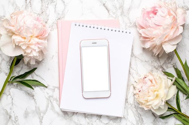 大理石の背景に白とピンクのノートブックとパイオニーの花と携帯電話