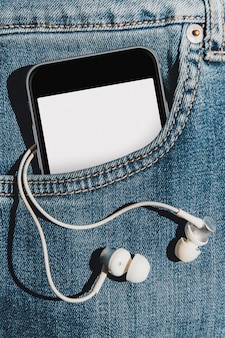 Mobile phone with blank mockup screen in the pocket of blue jeans with earphones