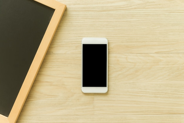 Mobile phone with blank screen and blank wooden blackboard frame on wooden table background. top view with copy space. can be used mock up image. vintage effect style pictures.