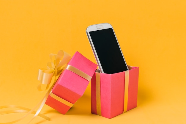 Mobile phone with blank screen in pink gift box