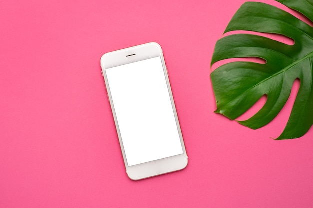 Mobile phone with blank screen and tropical leaves monstera on on neon pink background. top view, copy space, flat lay