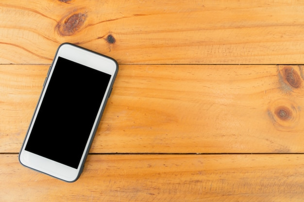 Mobile phone with blank screen on wooden table background. top view with copy space.