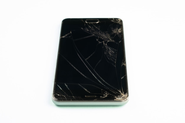 Mobile phone with broken black screen, top view. distressed damaged smartphone in pale green background, shallow depth of field