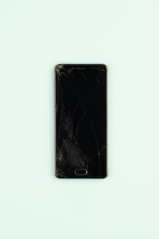 Mobile phone with broken black screen, top view. distressed damaged smartphone in pale green background, vertical shot