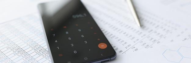 Мобильный телефон с калькулятором, лежащим на документах крупным планом, рассчитывая концепцию счетов