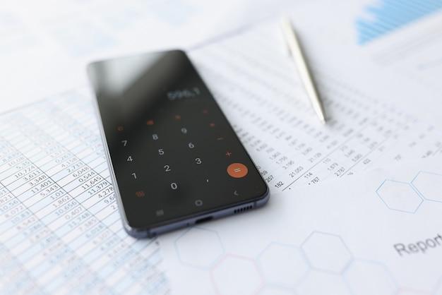 Мобильный телефон с калькулятором, лежащим на документах крупным планом