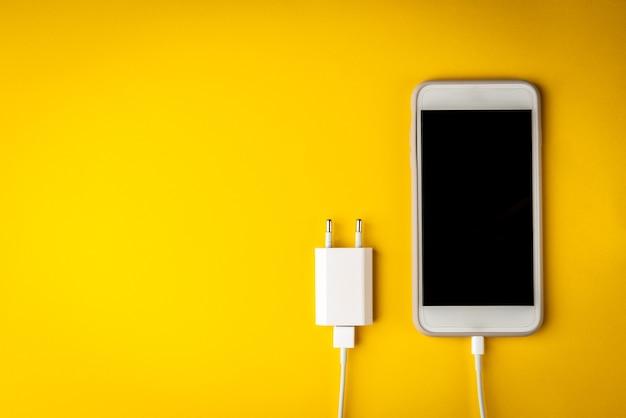 Мобильный телефон с зарядкой на желтом фоне.