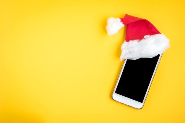 黄色のクリスマス帽子の携帯電話。