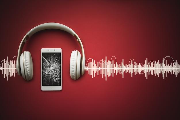 오디오 트랙이 있는 빨간색 배경에 빈 깨진 검은색 화면과 이어폰이 있는 휴대 전화.