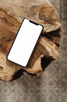 頑丈な木製のスツールとカーペットに空のコピースペースのモックアップが付いた携帯電話。フラットレイ、上面図。