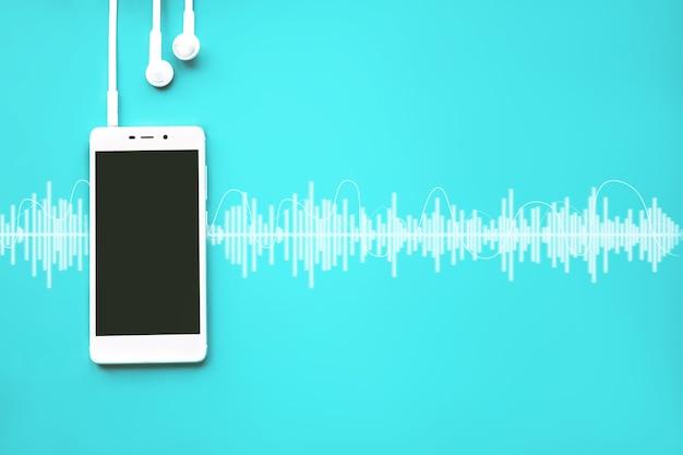 오디오 트랙이 있는 청록색 배경에 빈 화면과 이어폰이 있는 휴대 전화.