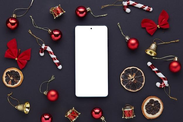 黒いテーブルの上の空の画面を持つ携帯電話。クリスマスの飾り。