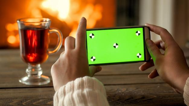 燃える暖炉に対して緑色の画面を備えた携帯電話。あなたのデザインのための場所