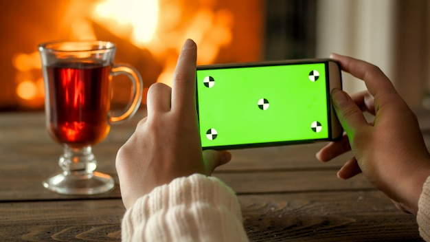 Mobile phone with green screen against burning fireplace. place for your design
