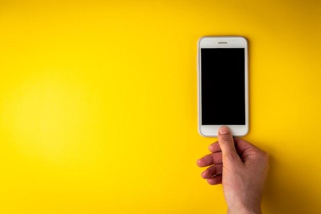 노란색 바탕에 손으로 휴대 전화입니다.