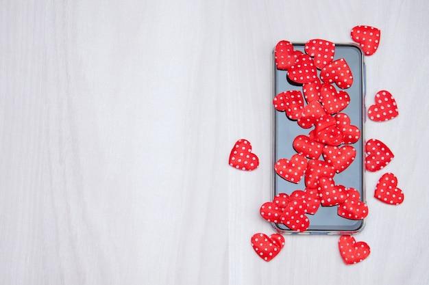 Мобильный телефон с сердечками, любовью, концепцией дня святого валентина. нравится и нравится время.